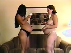Two pregnant babes strip and fondles their tits in the living room